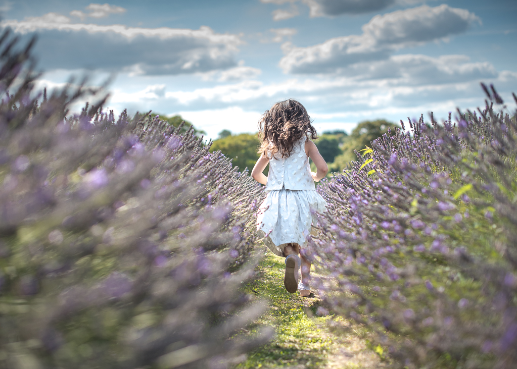 Girl running through a lavender field