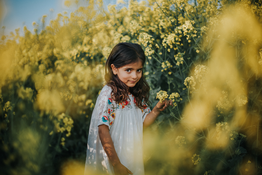 Outdoor photography session of a young girl in a rapeseed field