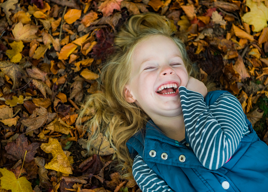 A little girl photographed playing with the autumn leaves