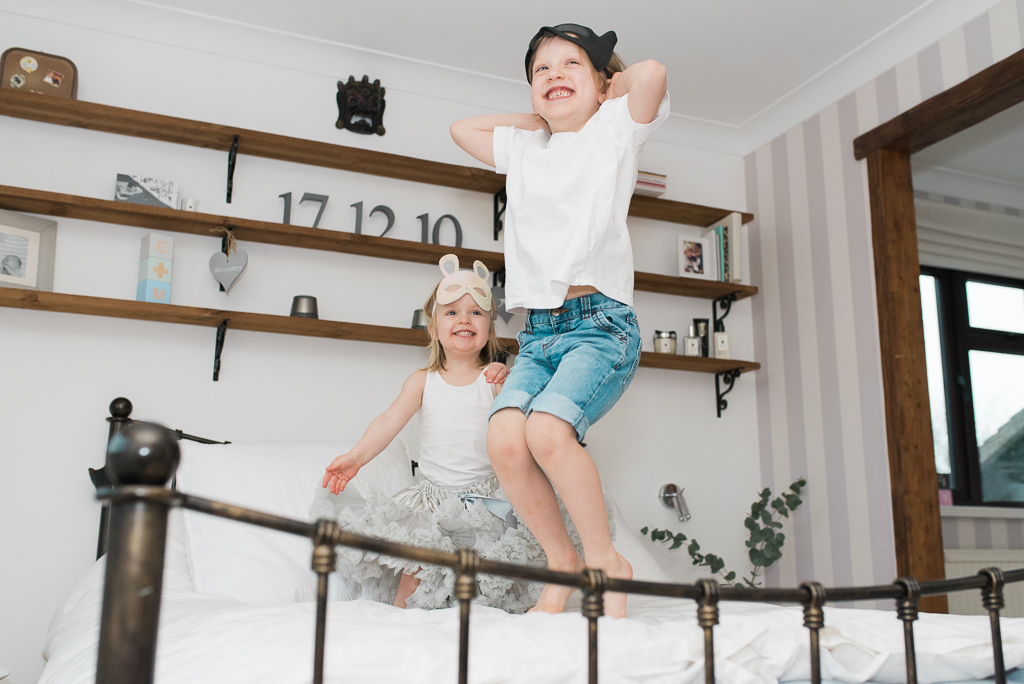 At home children jumping on bed photoshoot