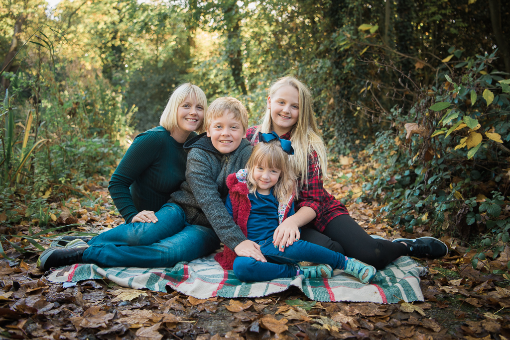Family Portrait of a mother and her children all sitting on a rug in the woods