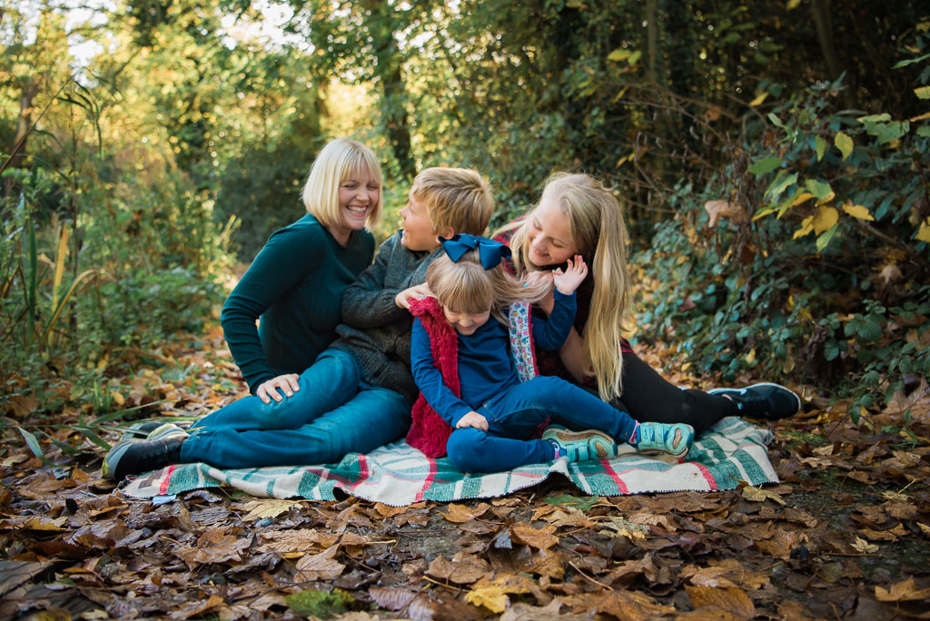 Family Portrait of a mother and her children in the woods sitting on a rug