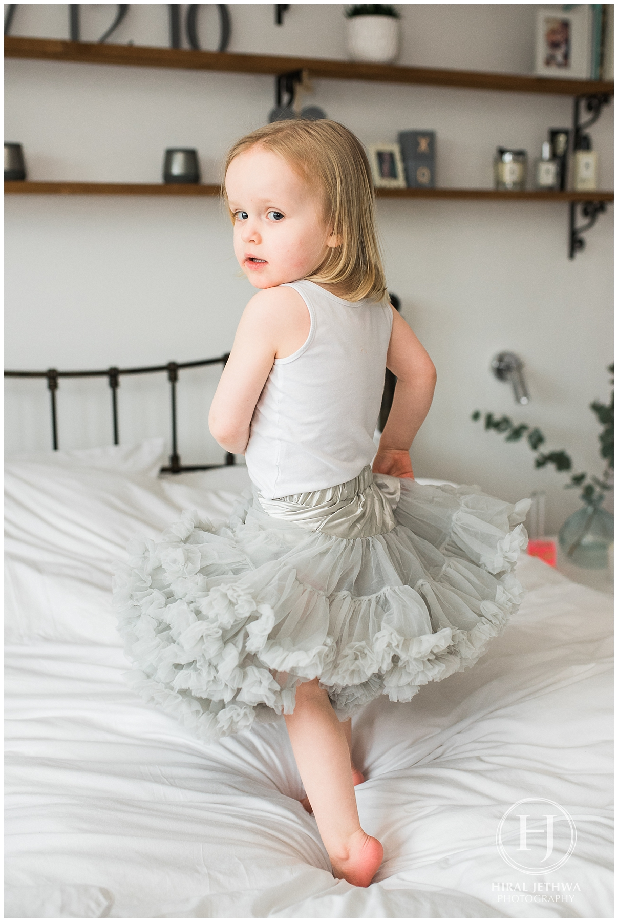 Little girl dressed up and dancing on her mums bed