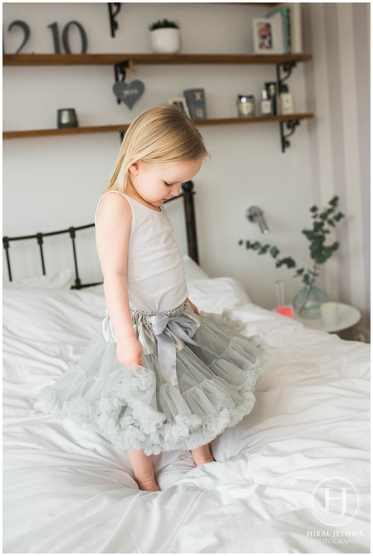 Little girl dressed up and playing on her mums bed